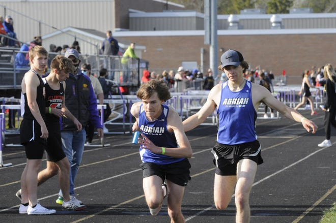 Adrian's Ben Schefka, foreground, takes the handoff from Christian Fischer in the 4x800-meter relay event at Friday's Onsted Early Bird Invitational.
