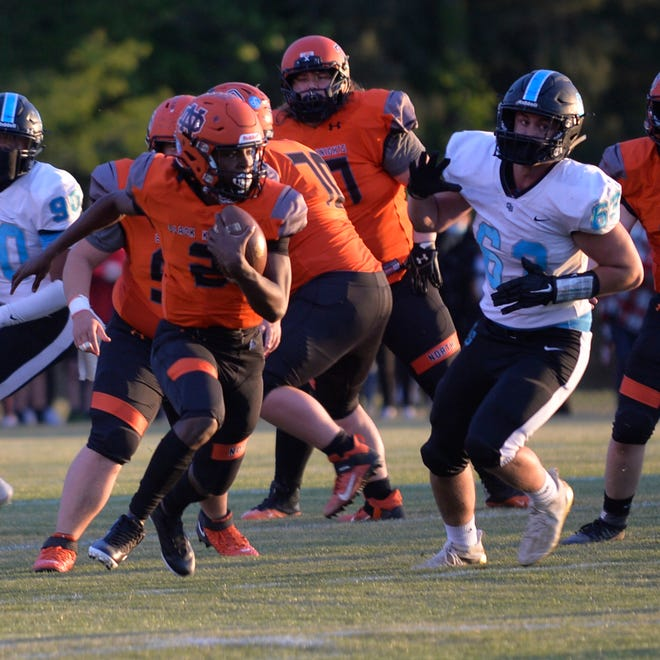 North Davidson quarterback Tedric Jenkins runs as Oak Grove's Hunter Grieser gives pursuit in Friday's second-round 2-AA state playoff game. Jenkins threw two touchdown passes in North Davidson's 34-23 win. [Mike Duprez/The Dispatch]