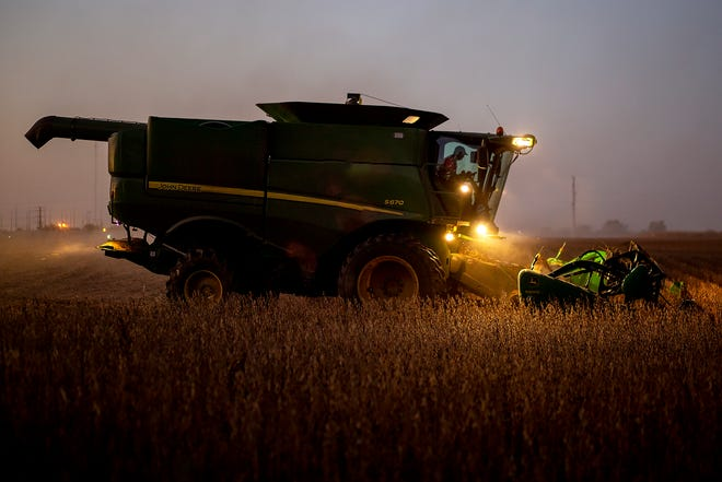 Jim Inness with James Inness Farms combines soybeans just after sundown along East Fremont Street on Tuesday, Oct. 6, 2020.