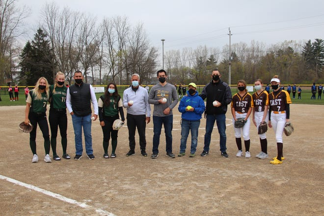 Gentex CFO Kevin Nash (third from left), Zeeland Mayor Kevin Klunstra (middle left), Zeeland LL president Brandon LaRosa (middle right) Youth Sports Coordinator Kelli Kloss (fifth from right) and Brett Geertsma, the city's recreation director (fourth from right) pose with softball players from Zeeland East and West after throwing out the ceremonial first pitch