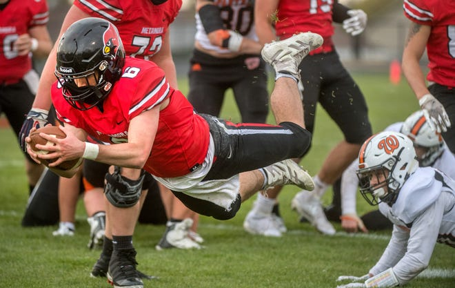 Metamora quarterback Connor Willerton (6) dives for extra yardage on a run against Washington in the first half Friday, April 23, 2021 in Metamora.