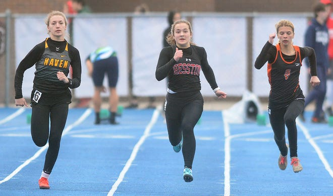 Caryn Yoder of Hesston battles Reese Roper of Haven, left, and Breanne Peters of Smoky Valley, right, in the finals of the 100-meter dash at the 50th Conrad Nightingale Invitational. Yoder led a 1-2 Hesston finish in the event. The Swathers took third in the team standings.