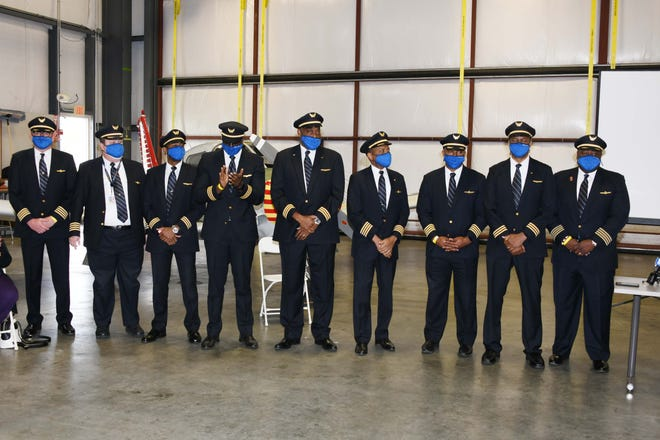 Nine United Airlines pilots who graduated from DSU's Aviation Program gather for a group shot during the event.