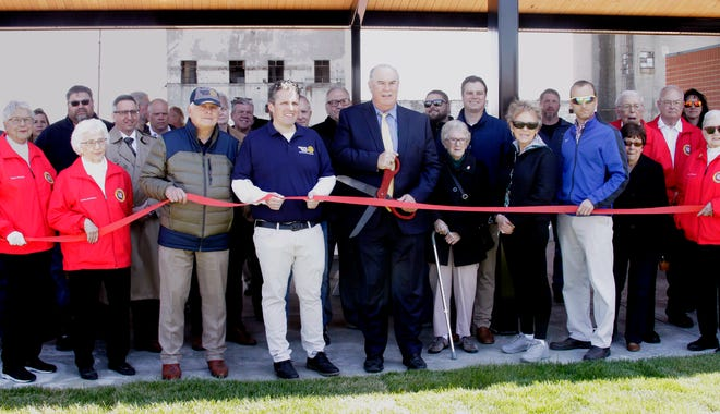 Moberly Mayor Jerry Jeffrey holds a large size set of scissors as he is surrounded by many persons that attended a ribbon cutting ceremony held Thursday, April 22, to officially announce the opening and public use of a pavilion and restroom facility at Depot Park.