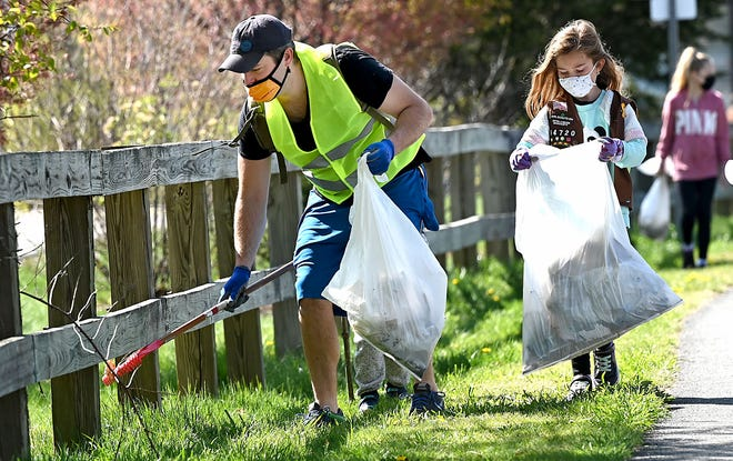 David Schwenke of Milford picks up trash along the Upper Charles Rail Trail during the Citizens for Milford's sixth Milford Beautification Day on Saturday. Also helping out were his Girl Scout daughters Lily, 8, and Julie, 7