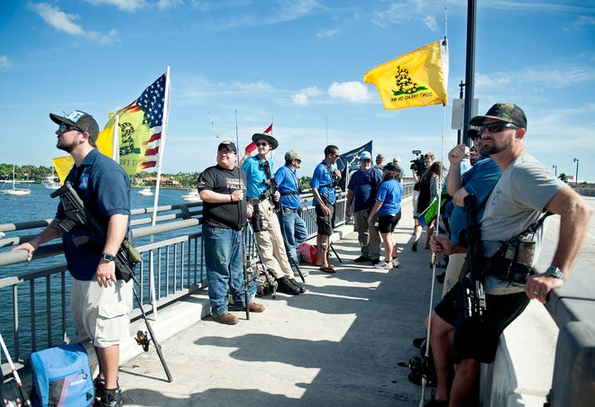 Holding fishing poles, Florida Carry members gather during the Palm Beach 2nd Amendment Fishing Gathering in early January 2020, on the West Palm Beach side of Royal Park Bridge.