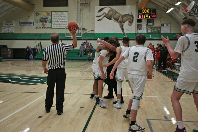 As time runs out, the Burros embrace on the court after defeating Oak Hills at home.