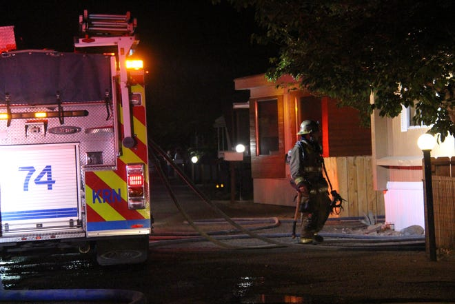 A Kern County fireman checks out an abandoned trailer in the Town and Country trailer park Friday night. The Kern County Fire Department extinguished a blaze in the trailer with the help of the Ridgecrest Police Department, who stopped traffic on North Norma Street to run a water line across the street.
