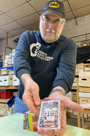 "Tom Mattevi, owner of Comics, Cards and Collectables in Canton, displays a replica trading football card of ""Flash Gordon."" Mattevi's shop is marking the 40th anniversary of the ""Flash Gordon"" movie by hosting a visit Saturday by actor Sam J. Jones."