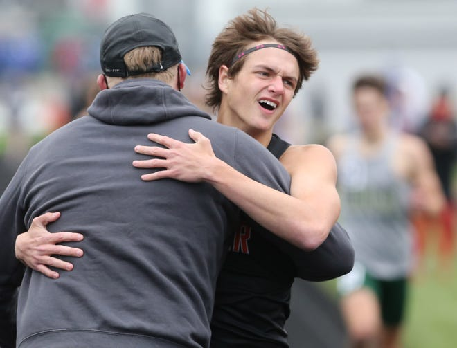 John Hollon of Hoover gets a hug after winning the 800 meter run during the Stark County Track and Field Meet at Perry on Saturday, April 24, 2021.