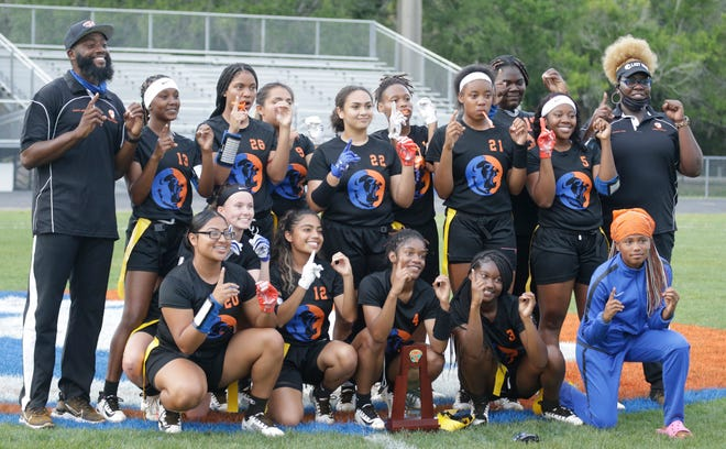Members of the Southeast High flag football team post with the first-place trophy after defeating Seminole Osceola, 32-12, in the Class 1A-District 12 final Friday night at Paul Maechtle Field at John Kiker Memorial Stadium.