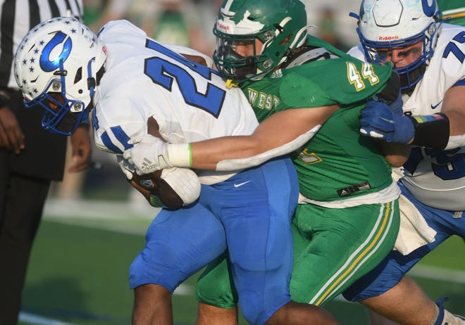 West Brunswick's Carter Wyatt makes the tackle against Clayton's Dashawn Hinton in the second round of the 3AA playoffs at West Brunswick High School in Shallotte, N.C., Friday, April 23, 2021.   [MATT BORN/STARNEWS]