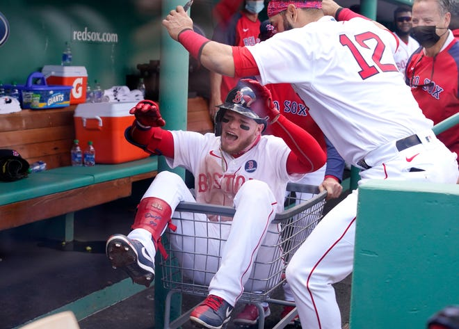 Boston Red Sox's Alex Verdugo is pushed through the dugout in a basket as he celebrates his solo home run with teammate Marwin Gonzalez (12) against the Chicago White Sox on Patriots Day at Fenway Park.