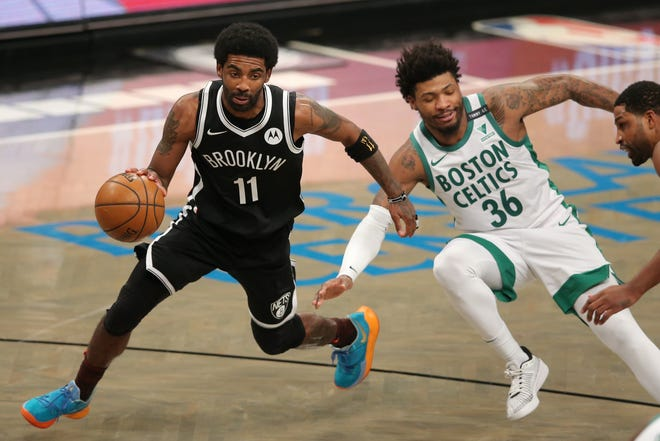 Nets point guard Kyrie Irving (11) dribbles the ball past Celtics point guard Marcus Smart during Friday night's third quarter in Brooklyn.