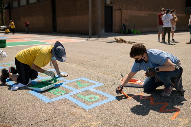 From left, Benjavan Upatising, a volunteer from UMass Memorial Health, and Brynn Bailey, a volunteer from Hanover Insurance, paint hopscotch squares Saturday at McGrath Elementary School as part of the Working for Worcester Build Day.