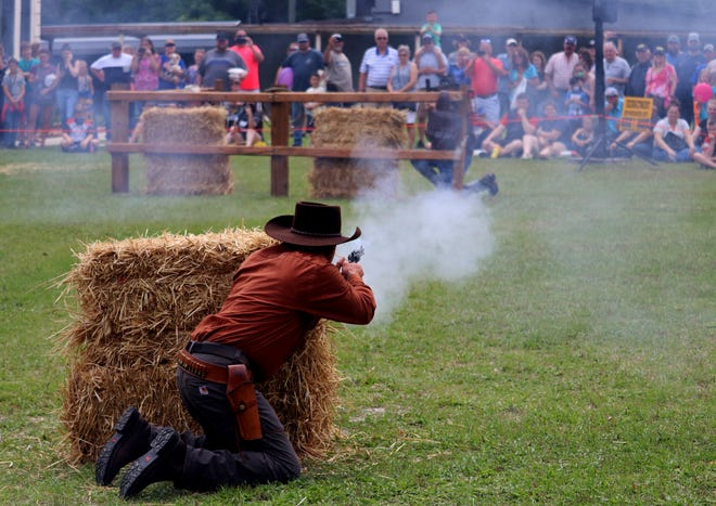 Gunfighters shoot at each other during a show at the Pioneer Days Festival at James Paul Park in downtown High Springs on Saturday.