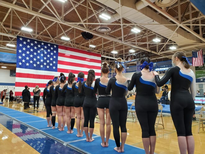 The Central High School co-op gymnastics team stands for the national anthem prior to competing in the Class 4A team competition at Thornton High School on Friday. [Courtesy photo/Holly Ward]