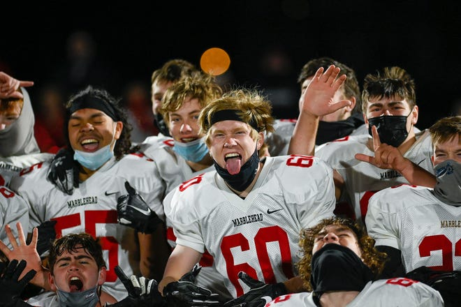 Marblehead football players celebrate the 34-7 win over Swampscott at Blocksidge Field in Swampscott on Friday, April 23 to end the season on top of the NEC with a 7-0 record.