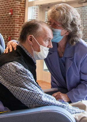 Flora Tackett kisses her husband Lloyd's forward during an emotional visitation at the VA Memorial Hospital on April 23, 2021.  The two had need seen one another in person in over a year due to the coronavirus pandemic.