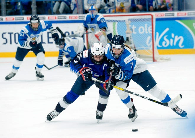FILE - Kendall Coyne Schofield, left, of the United States and Nelli Laitinen of Finland vie for the puck during the IIHF Women's Ice Hockey World Championships final match between the United States and Finland in Espoo, Finland, in this Sunday, April 14, 2019, file photo.