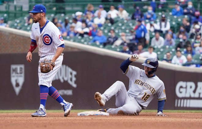 Brewers first baseman Keston Hiura slides safely into second base with a double as Cubs second baseman Eric Sogard waits for the throw during the fifth inning.