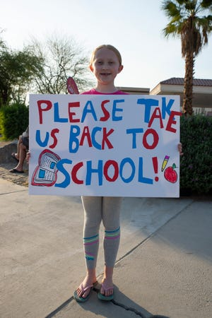 Emma Harper, a third grade student at James Monroe Elementary School, shows off her sign in support of a full return to in-person learning.