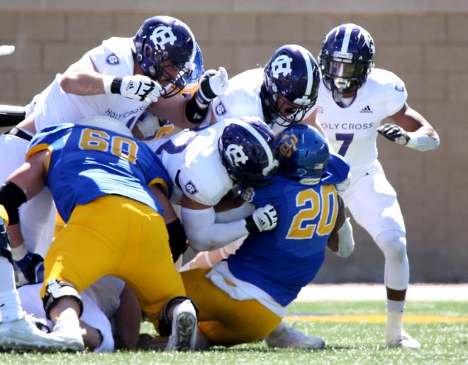 A host of Holy Cross tacklers greet South Dakota State running back Pierre Strong during Saturday's playoff game.