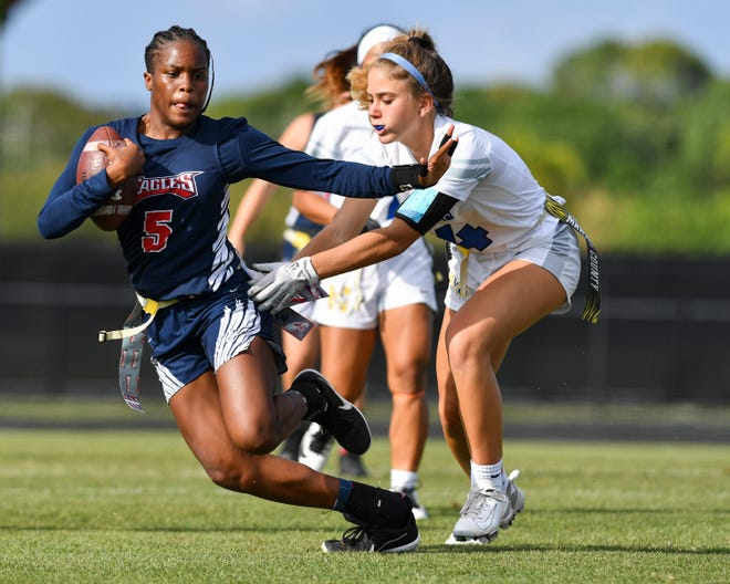 Centennial's Tamya Heath (5) gains yardage as Martin County's Natalie Belisle (4) defends in a flag football District 10-2A championship on Friday, April 23, 2021, at Martin County High School in Stuart. Centennial won 19-13 in two overtimes.