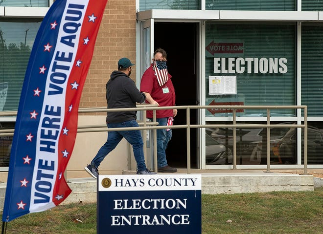 Election clerk Wes Garcia, right, holds the door for a voter at an early voting location at the Hays County elections office in the Hays County Government Center in San Marcos last year.