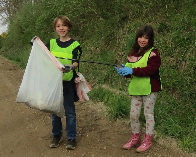 Nolan Angle, 10, and his sister, Emalie, 6, of Killbuck, pick up trash along Brinkhaven Road during the Rally in the Valley road cleanup on Saturday.