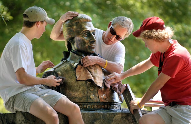 Boy Scout John Duggan (right) shines the bust of Samuel Hammond on Greene Street in 2006 with the help of his father and brother. Hammond was a soldier, congressman and state legislator, among many other roles.
