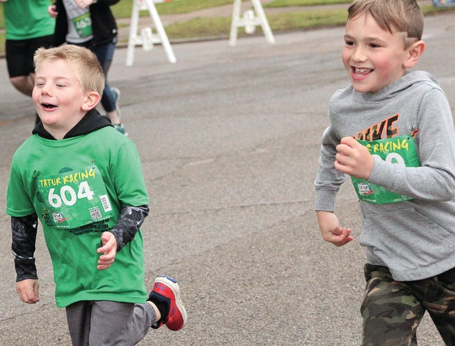 Thomas Baker-Lowe, left, and another boy enjoy the moment during the early stage of Saturday's Shamrock run.