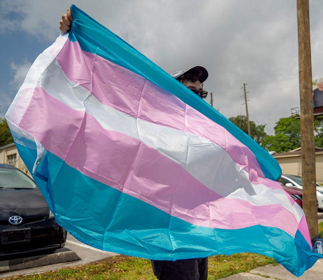 A demonstrator holds a flag at a rally supporting transgender youth in Lady Lake on April 25. [Paul Ryan/Correspondent]