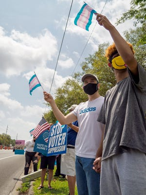 Demonstrators hold up signs and flags at a rally supporting transgender youth in Lady Lake on Sunday, April 25, 2021. [PAUL RYAN / CORRESPONDENT]
