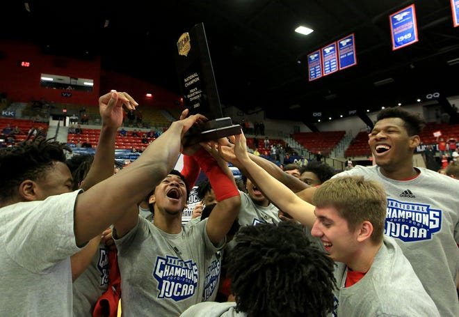 Coffeyville players hold up the championship trophy after defeating Cowley 108-99 in the NJCAA Men's DI National Basketball Championship Saturday at the Sports Arena.