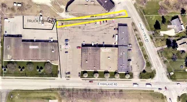 This aerial view shows the multi-tenant building at left on East Highland Road where IL Logistics will occupy space and park box trucks in the back. Molon Labe Crossfit is among tenants in the building at right.