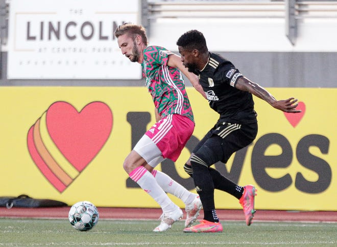 Energy FC midfielder Villyan Bijev fights for possession of the ball with FC Tulsa defender Bradley Bourgeois on Saturday night at Taft Stadium.