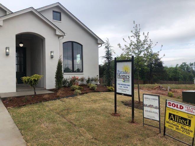 """Signs of the times in the housing market: left, Parade of Homes Spring Festival; the builder of this entry at 2433 Amante Court in Ednond, Ripple Creek Homes; the Realtor's """"Sold"""" sign."""