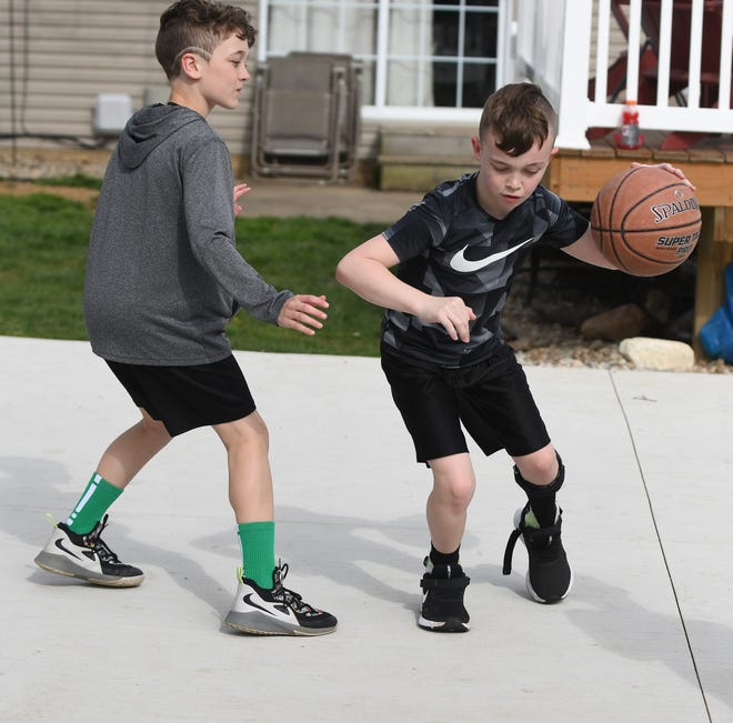 Nash Rohr, 9, (right) plays a game of basketball with his older brother, Alex. Alex's travel basketball team sported green socks to support his little brother who has cerebral palsy.