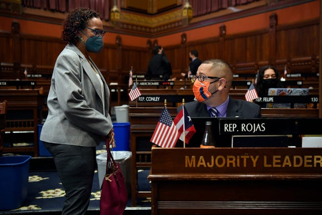Connecticut House Majority Leader Jason Rojas, D-East Hartford, right, speaks with state Rep. Toni Walker, D-New Haven, left, during an April 19 session at the State Capitol in Hartford.