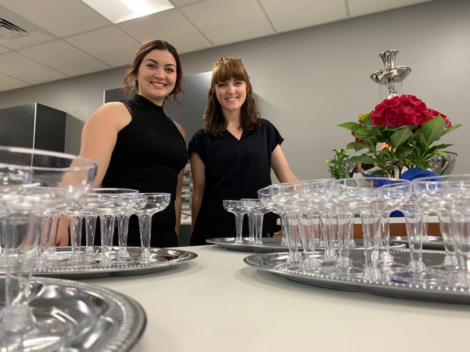 Shelby Herring, left, and Rebekah Taylor, right, pose for a photo in the kitchen area of their new event venue, The Eleven Hundred. Herring and Taylor celebrated the grand opening of the venue Saturday with an open house.