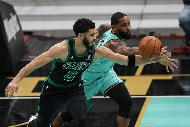 The Hornets' Brad Wanamaker (right) battles the Celtics forward Jayson Tatum for a loose ball in the second half Sunday in Charlotte.