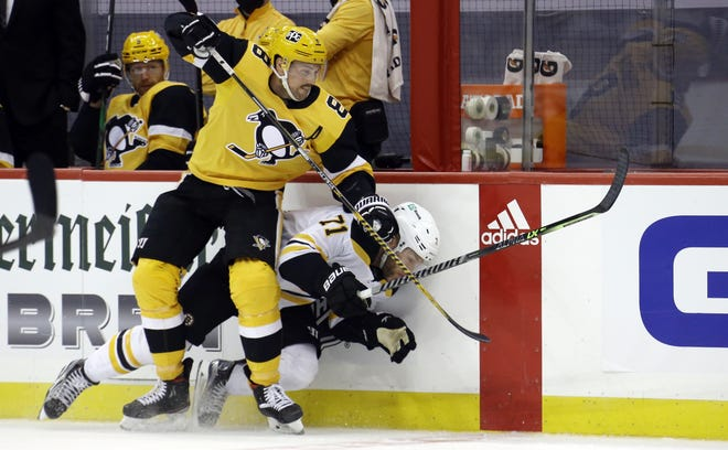 Penguins defenseman Brian Dumoulin (8) checks  Bruins left wing Taylor Hall into the boards during the second period Sunday at Pittsburgh.