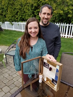 Alyssa and Brian Bostic stand with a shadow box that memorializes Hope and Poppy.