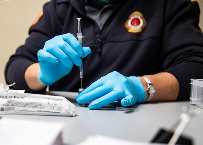 Shelly Hulbert, a lieutenant in the Memphis Fire Department, draws the COVID-19 vaccine from an ampule into a syringe at Calvary Episcopal Church on Sunday, April 25, 2021.