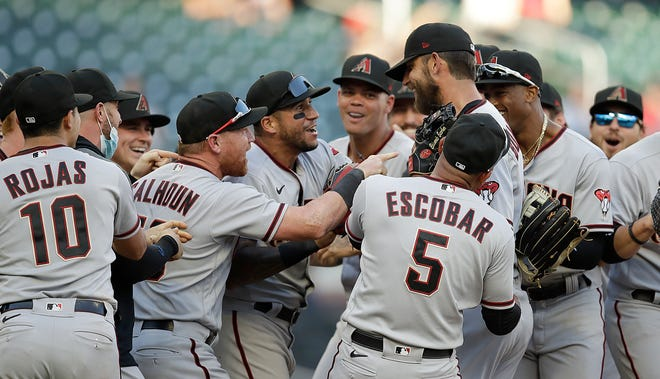 Arizona Diamondbacks pitcher Madison Bumgarner, center right, is congratulated after pitching a seven-inning no-hitter against the Atlanta Braves at the end of the second baseball game of a doubleheader Sunday, April 25, 2021, in Atlanta. (AP Photo/Ben Margot)