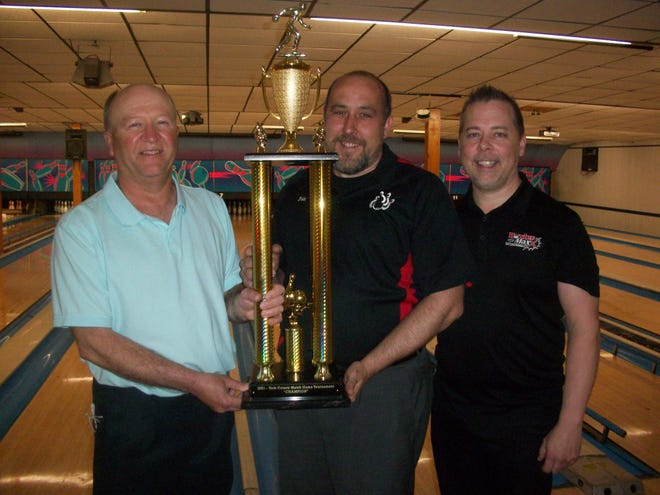 Eric Smith, center, accepts the BowlerMaxx York County Match Play Championship trophy from Mike Zelger of Lion Bowl, left, while Terry Miller of BowlerMaxx Pro Shop, looks on. Smith also won $1,000.