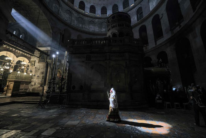 An Ethiopian Orthodox Christian worshipper walks around the Edicule, the place believed to be where Jesus Christ was buried, during Palm Sunday celebrations at the Church of the Holy Sepulchre in Jerusalem April 25, 2021.