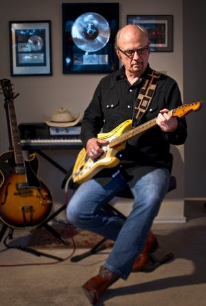 """Denny Freeman poses in November 2012 at his home in Austin with one of his favorite guitars, the 1957 reissued Fender Stratocaster. """"I kinda feel like I've spent my whole life preparing for this gig,"""" Freeman told friends after he became a touring guitarist in Bob Dylan's band. """"Never thought I'd be playing a solo on 'Lay Lady Lay,' though."""""""