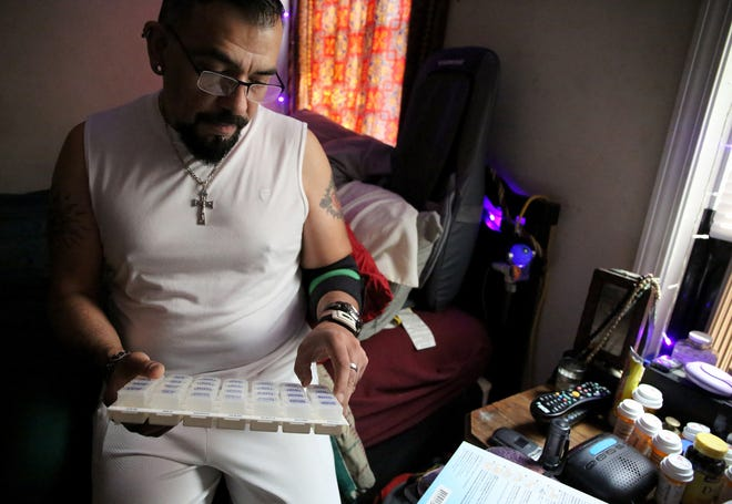 Greg Sanchez, who had been living with HIV for 30 years, displayed his many medications stored in the bedroom of his Chicago home in 2015. [ANTONIO PEREZ/CHICAGO TRIBUNE/TNS/FILE]